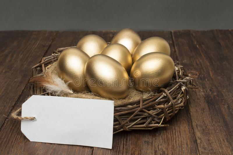 Nest with golden eggs with a tag and place for text on a wooden background. The concept of successful retirement stock image