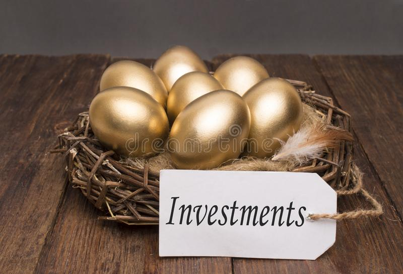 Nest with golden eggs with a tag and a word of investments on a wooden background. The concept of successful retirement stock photography