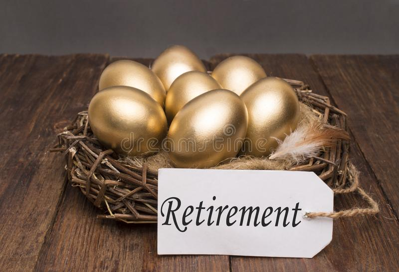 Nest with golden eggs with a tag and a word retirement on a wooden background. The concept of successful retirement stock photos