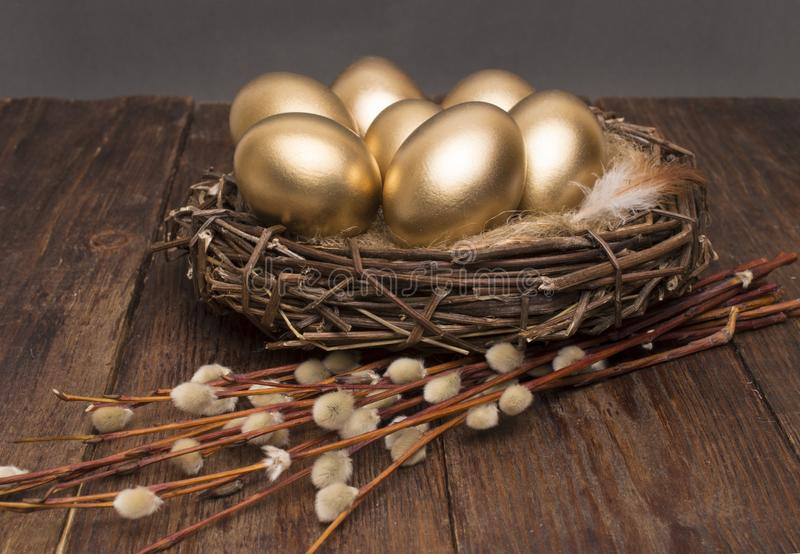 Nest with golden eggs with willow on a wooden background. Easter. royalty free stock image