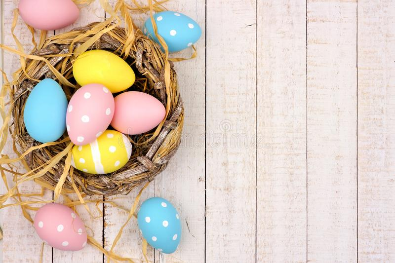 Nest side border with pink, yellow & blue Easter Eggs against white wood stock photos