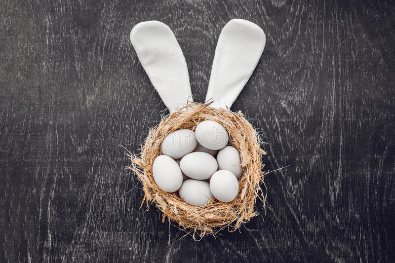 A nest with three white Easter eggs and bunny ears at home on Easter day. Celebrating Easter at spring. Painting eggs royalty free stock images
