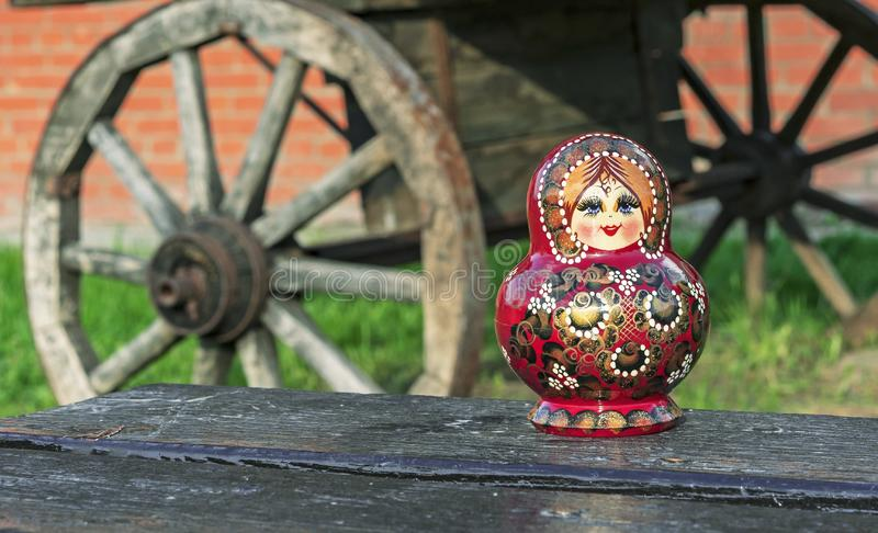 Nested doll on the background of an old wooden cart. Matryoshka is a national Russian souvenir royalty free stock photography