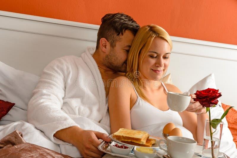 Nestelende het bed van de paar romantische ochtend het drinken koffie royalty-vrije stock afbeeldingen