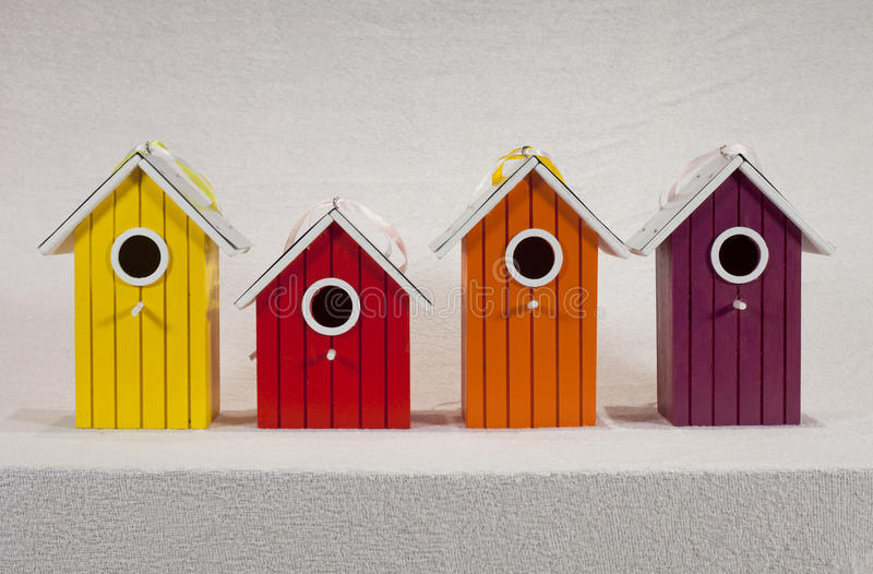 Nesting bird houses. Nesting houses in yellow, red, orange and violet colours, with one house smaller then others royalty free stock images