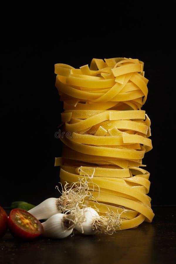 Nestnoedels met kersentomaten en tedere garlics royalty-vrije stock afbeeldingen