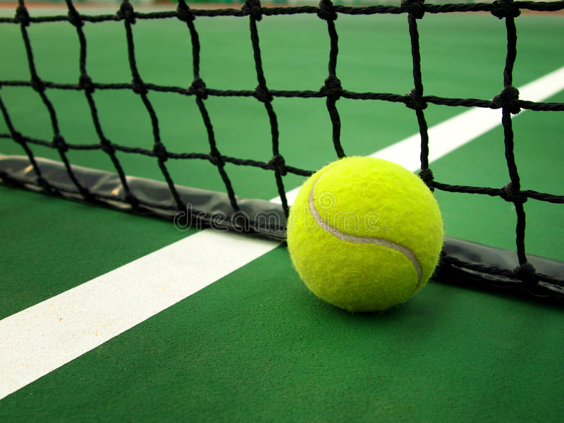 Net and Ball. Tennis net and tennis ball on the court stock photos