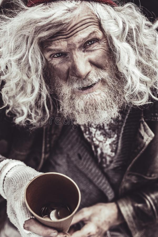Portrait of homeless holding cup with alms and looking into camera. stock image