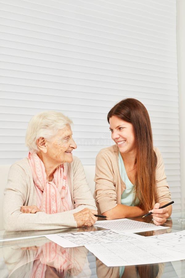 A neta ajuda a avó com treinamento da memória foto de stock