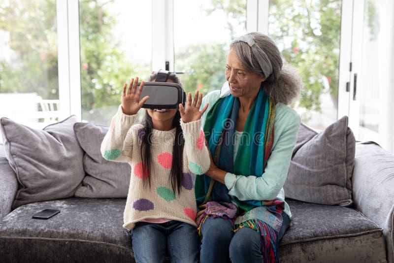 Neta com a avó que usa auriculares da realidade virtual na sala de visitas imagem de stock