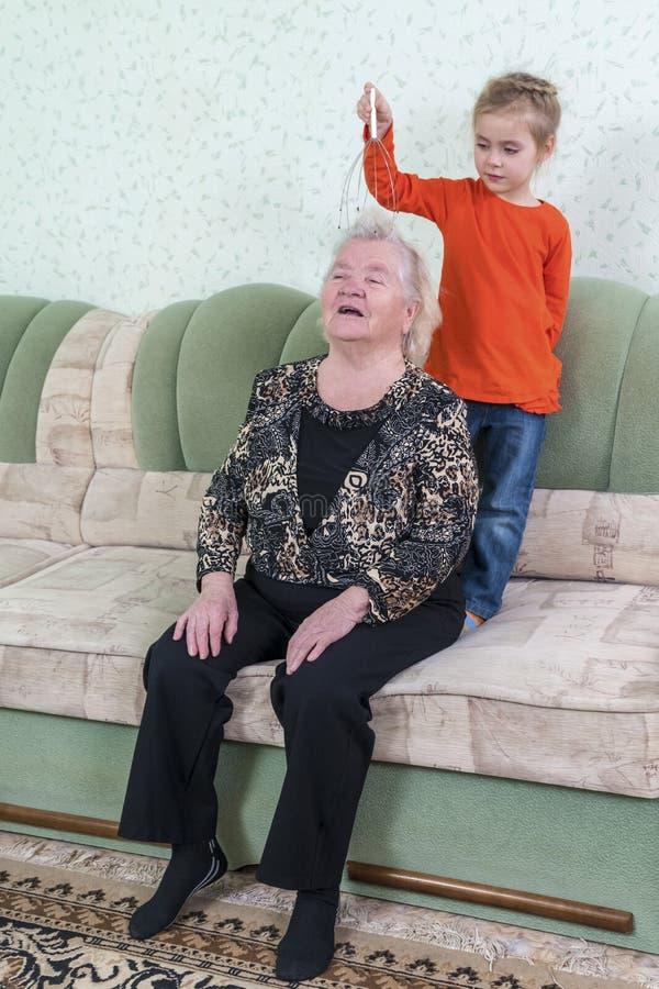 A neta faz massagens a cabeça da avó fotografia de stock royalty free