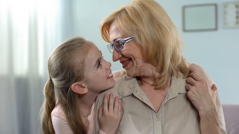 Neta loura bonita que abraça sua avó com amor, cuidado, apoio fotografia de stock royalty free