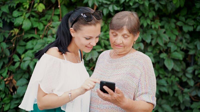 A neta mostra a avó idosa algo no smartphone, ensina-a segurar com dispositivo moderno e tecnologia fotografia de stock royalty free