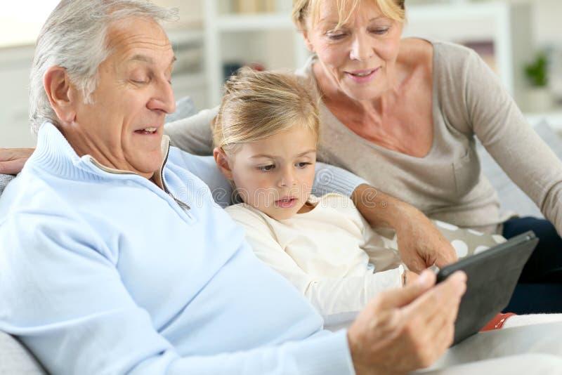 Neta pequena com as avós que usam a tabuleta no sofá imagem de stock
