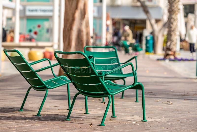 15/12/2018 Netanya, Israel, sillas de la calle del hierro para los transeúntes se encadena a la costa en un invierno caliente fotos de archivo