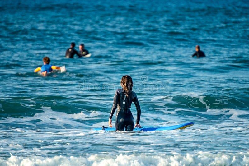 12/18/2018 Netanya, Israel, una persona que practica surf con un tablero va a nadar en el océano en el amanecer del día foto de archivo libre de regalías