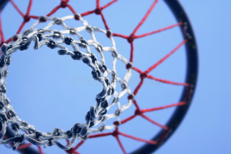 Netball net and hoop. A netball net abstract shot from below the goal post. Red white and blue netting material. Composition of the hoop and netting material