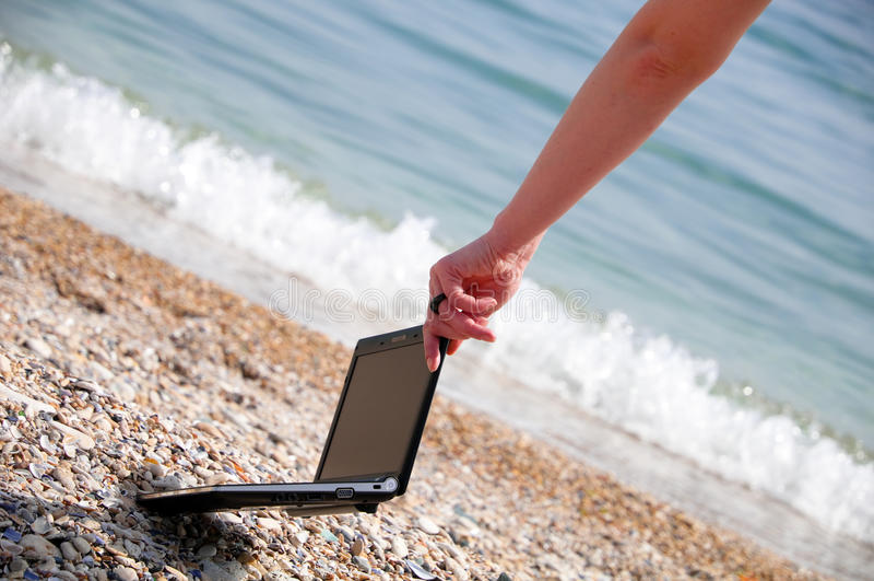 Netbook en la playa imagen de archivo