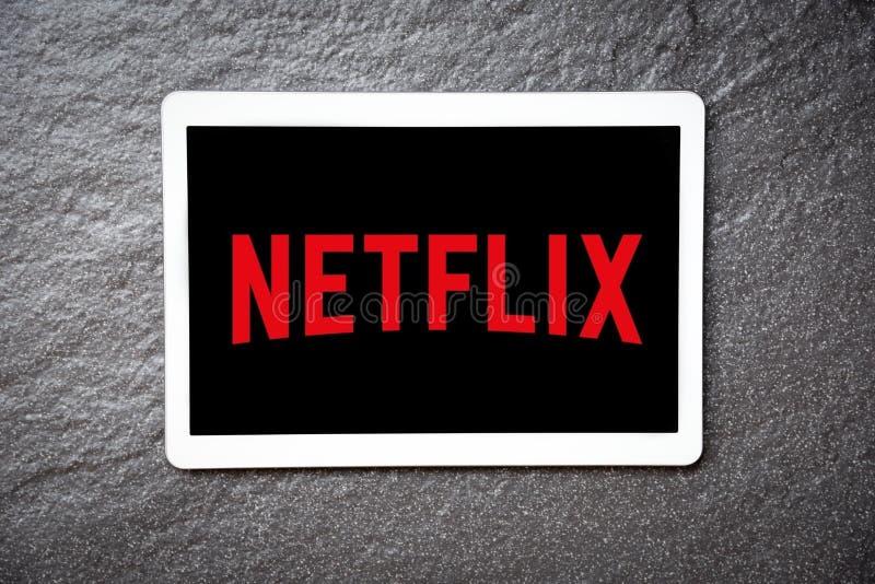 Netflix app på hållande ögonen på underhållning och filmer för minnestavlaservice med den Netflix logoen arkivbilder