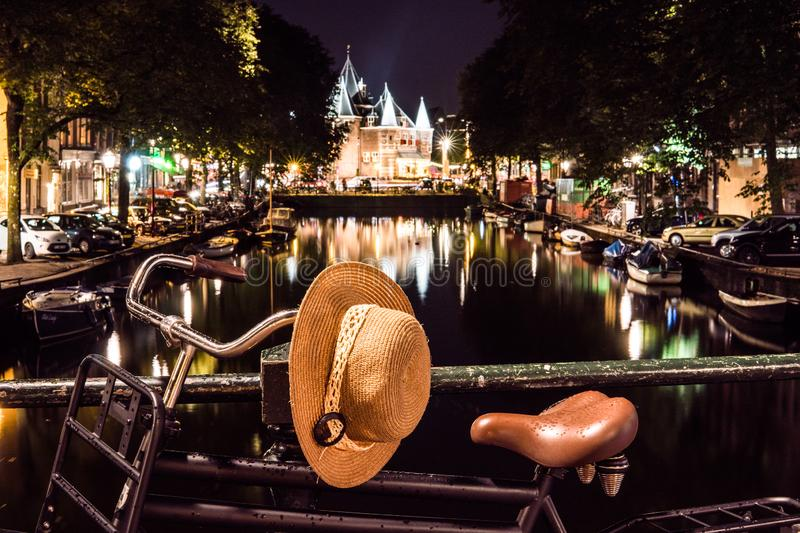 NETHERLANDS, AMSTERDAM - 23 AUG 2018: Night city view of bicycle with Hat on helm on Amsterdam bridge and typical dutch stock image