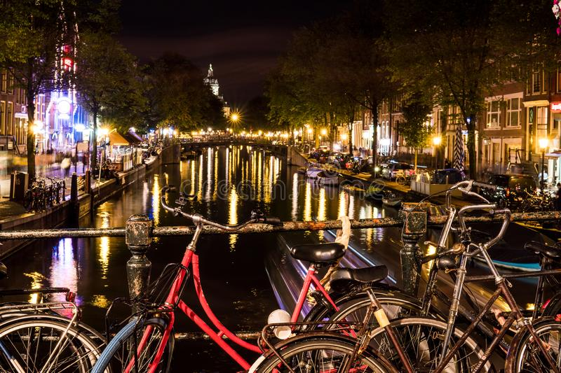 NETHERLANDS, AMSTERDAM - 23 AUG 2018: Night city view of bicycle on Amsterdam bridge and typical dutch houses, Holland stock photos