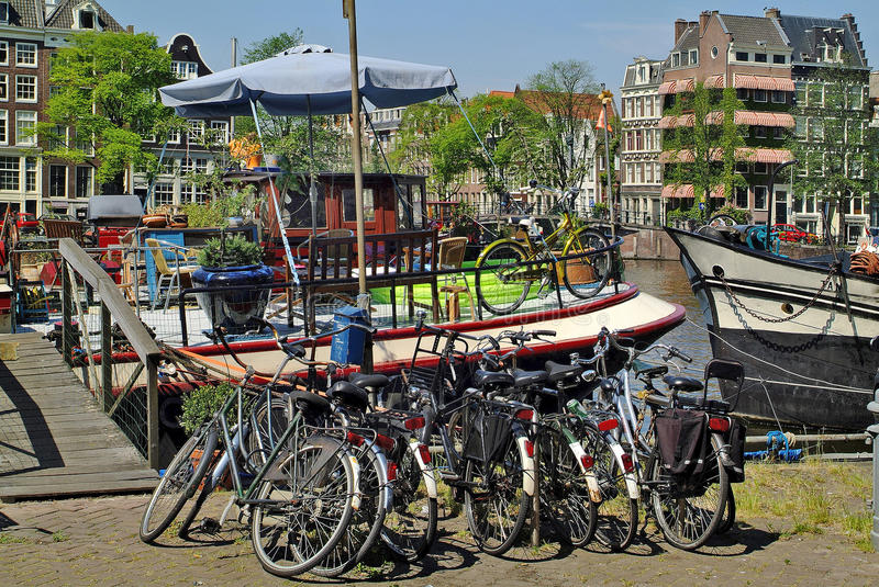 Netherlands, Amsterdam. Bicycles, houseboat and buildings on Amstel canal royalty free stock photography