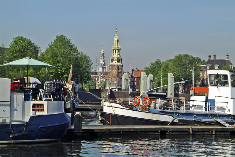Netherlands, Amsterdam. Boats and Montelbaans tower with Zuider church behind royalty free stock image