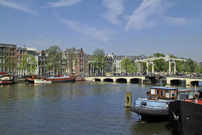 Netherlands, Amsterdam. Buildings in traditional structure and boats on Amstel river stock photos