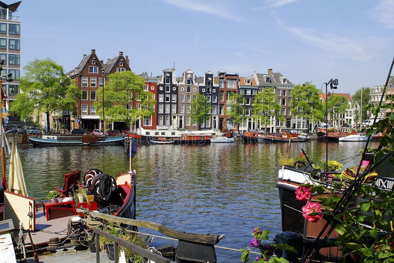 Netherlands, Amsterdam. Buildings in traditional structure and boats on Amstel river royalty free stock image