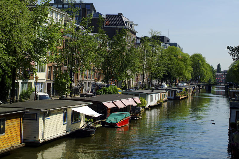 Netherlands, Amsterdam. House boats and buildings on Oide Schaans canal royalty free stock image