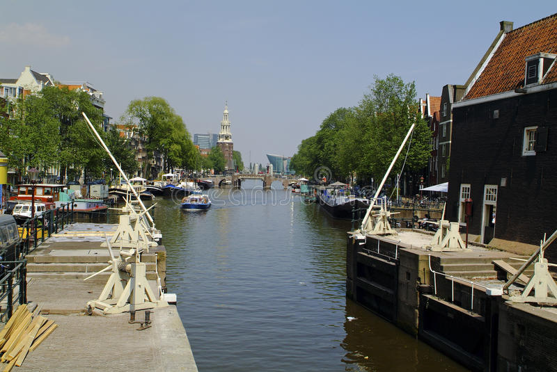 Netherlands, Amsterdam. Old lockage and cruising boat, Montelbaanstoren tower in background stock images