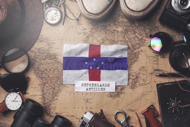 Netherlands Antilles Flag Between Traveler`s Accessories on Old Vintage Map. Overhead Shot.  royalty free stock images