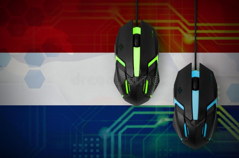 Netherlands flag and two mice with backlight. Online cooperative games. Cyber sport team. Netherlands flag and two modern computer mice with backlight. The stock photography