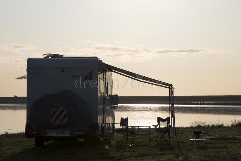 Camper and sun rise on Wadden sea. Netherlands,Friesland,Waddensea, july2018: Camper and sun rise on Wadden sea stock photo