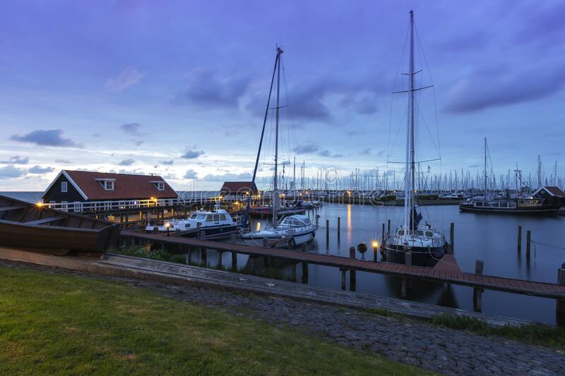 The Netherlands - Hindeloopen - a magical view of the evening harbor lit by lamps and the stone path leading to a wooden pier. Where sailboats and boats are royalty free stock photography