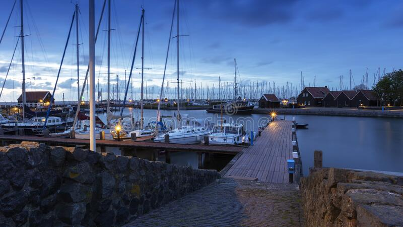The Netherlands - Hindeloopen - a magical view of the evening harbor lit by lamps and the stone path leading to a wooden pier. Where sailboats and boats are stock image