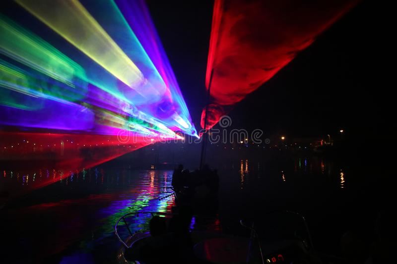 Laser show during public free event on public street and water with small ships parad royalty free stock images