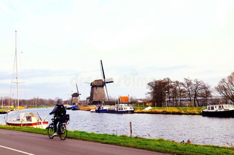 Netherlands Typical Scenery, Dutch Windmills, Holland Canal, Alkmaar Boats, Waterfront Bicycle Ridel royalty free stock image