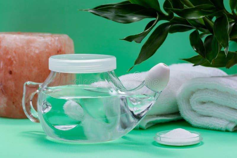 Neti罐,堆盐,竹叶子,在绿色背景滚动了白色毛巾和喜马拉雅盐蜡烛台 静脉窦洗涤 免版税库存图片