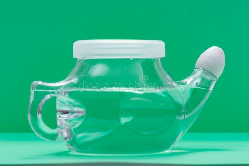Neti-Topf mit weicher Komfort-Spitze lokalisiert auf grünem Hintergrund Kurvenwäsche Nasensp?lung stockbild