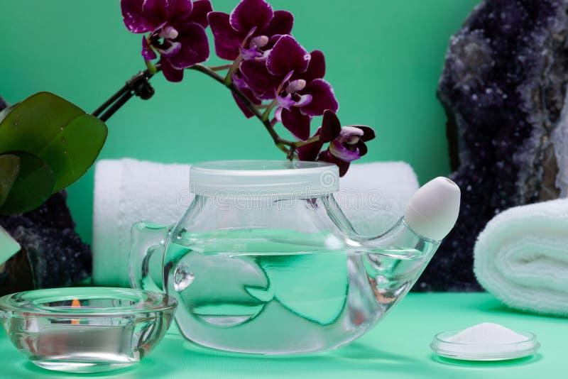 Neti-Topf, Stapel von salzigen, gerollten weißen Tüchern, von purpurroten Orchideen-Blumen und von Lavendel-Tee-Licht-Kerze auf g lizenzfreie stockfotos