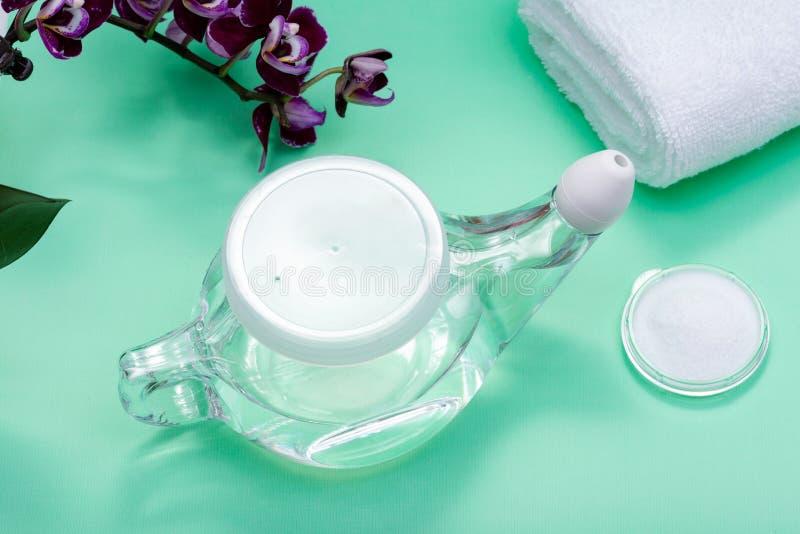 Netipot met Zacht Comfortuiteinde, stapel van Zoute, Purpere Orchideebloemen en opgerolde Witte Handdoeken op groene achtergrond  stock foto