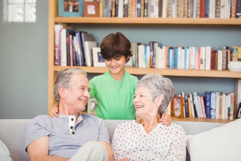 Neto com as avós na sala de visitas imagem de stock
