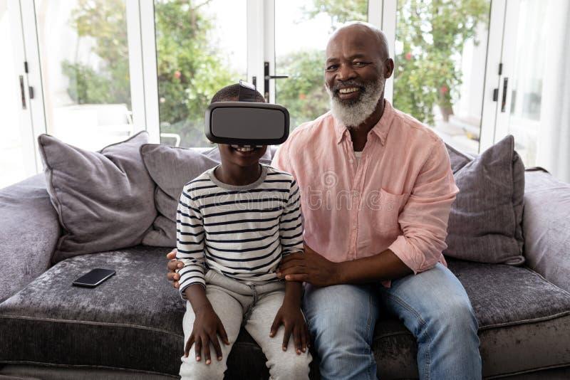 Neto com o avô que usa auriculares da realidade virtual na sala de visitas foto de stock royalty free