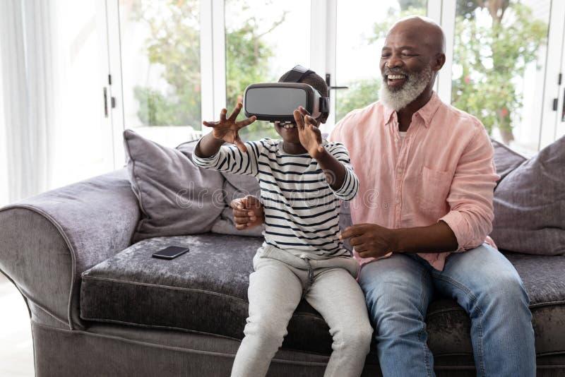 Neto com o avô que usa auriculares da realidade virtual na sala de visitas imagens de stock royalty free