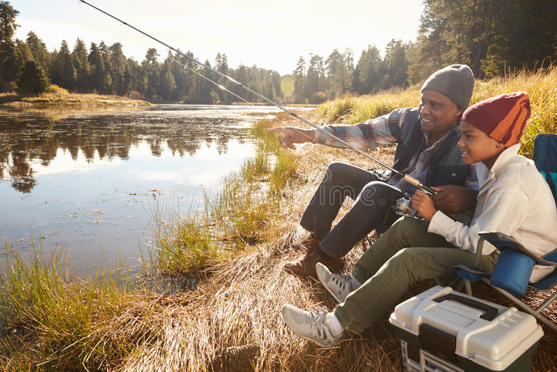 Neto de ensino de primeira geração a pescar pelo lago imagens de stock royalty free
