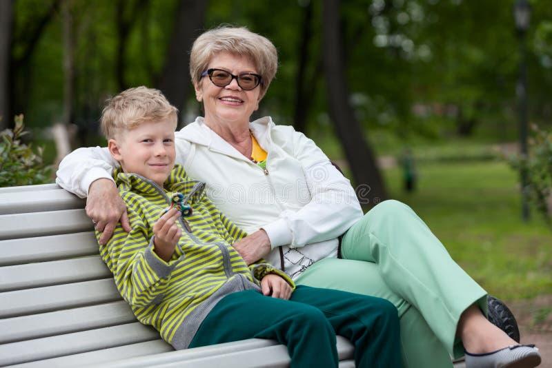 Neto de sorriso que joga com dispositivo do girador, avó feliz que abraça o menino, duas pessoas foto de stock royalty free