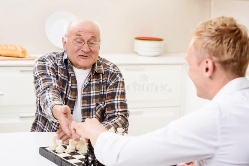 Neto e avô que jogam a xadrez na cozinha fotografia de stock royalty free