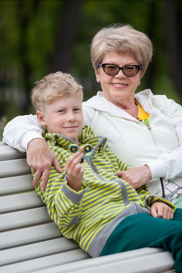 Neto novo que mostra o dispositivo novo do girador, avó superior feliz que abraça o menino no banco no parque no dia imagens de stock royalty free