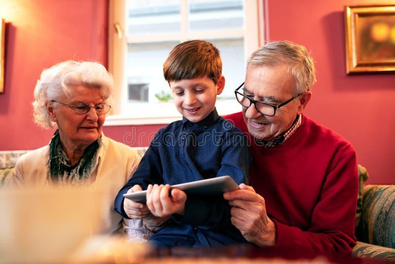 Neto que ensina a suas avós como usar uma tabuleta imagem de stock royalty free